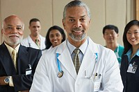 Middle-aged male African doctor with co-workers in the background
