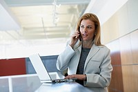 Businesswoman with laptop and cell phone