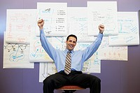 Businessman cheering in front of wall charts