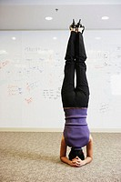 Businesswoman doing headstand in front of whiteboard wall
