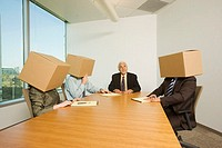 Businessman at meeting with co-workers who have boxes on their heads