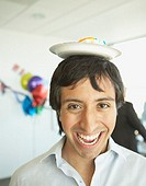 Hispanic businessman with a paper plate of cake on his head, Redwood City, California, United States