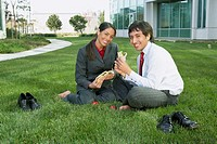 Hispanic businesswoman and businessman eating lunch in the grass, Redwood City, California, United States,