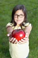 Girl holding apple in outstretched hands