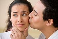 Studio shot of Hispanic man kissing Hispanic woman´s cheek
