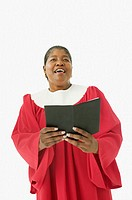 Studio shot of senior African woman wearing a choir robe and singing