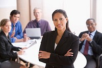 Hispanic businesswoman standing with coworkers in the background