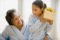 Hispanic granddaughter shaking wrapped gift with grandmother