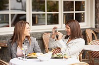 Woman having her photograph taken by other woman at lunch, Larkspur, California, United States