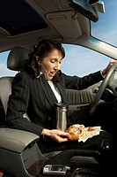 Businesswoman driving and eating, San Rafael, California, United States