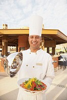 Hispanic male chef with plate of vegetables, Los Cabos, Mexico