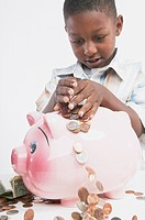 Young African boy putting money in a piggy bank, San Rafael, California, United States