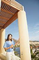 Woman standing on a balcony at a resort hotel, Los Cabos, Mexico