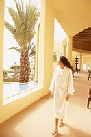 Woman walking in sunlit resort hotel hallway, Los Cabos, Mexico