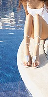 Woman sitting next to pool with shiny sandals