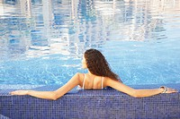 Woman leaning with arms outstretched on edge of pool