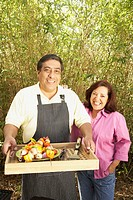 Hispanic couple with tray of kebabs outdoors