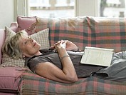 Mature woman lying on sofa with book on stomach, hands clasped
