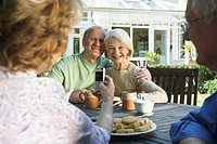Two senior couples sitting in garden, woman holding up camera phone