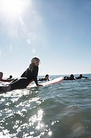 Group of friends swimming out to sea on surfboards