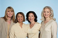 Four mature women standing side by side, smiling, portrait