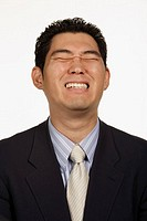 Young businessman making face, eyes closed, close-up