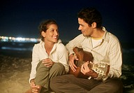 Couple sitting on beach, man playing guitar, at night
