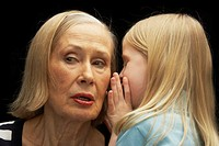 Granddaughter (5-7) whispering in grandmother´s ear, close-up