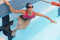 Mature woman pushing off from edge of swimming pool, elevated view