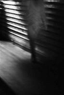 Person walking on sidewalk at night, blurred, b&w
