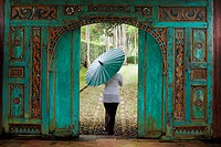 Woman walking through a traditional, nicely carved door at Losari Coffee Plantation in West Java, Indonesia, South East Asia