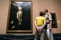 Couple looking at painting of the crucifiction inside the Museo del Prado, Madrid, Spain
