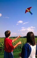 boy and girl flying a kite together