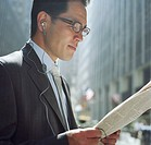 Businessman reading newspaper, wearing headset, side view