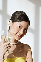 Woman holding wine glass, smiling at camera
