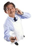 Mature man wearing apron, using mobile phone, holding spatula looking at camera