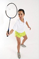 Woman hitting shuttlecock with badminton racket