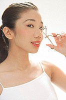 Woman holding eyelash curler to eye, looking at camera