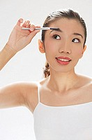 Woman brushing eyebrows