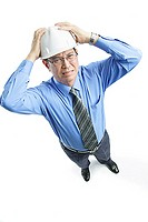 Man wearing hardhat frowning, hands on head