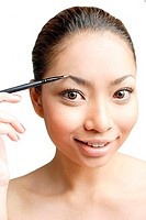 Young woman using eyebrow pencil