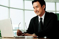 Businessman in office looking at laptop, smiling