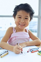 Young girl with crayons, smiling at camera