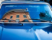 Brick building reflected in windshield in blue car.