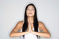 Woman practicing yoga, hands together, eyes closed