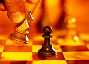 toned close-up of a hand moving the knight figure on a chessboard