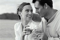 side view of a couple holding glasses of wine and looking into each others eyes (black and white)