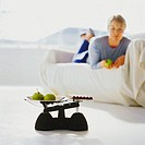 close-up of a weighing scales with apples on it and a woman on a sofa in the background
