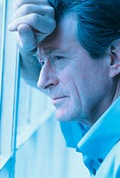 side profile of a introspective man leaning against a window pane