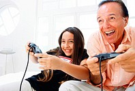 view of a girl (10-12) playing a video game with her grandfather